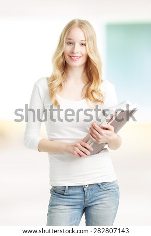 Portrait of smiling female student standing in front of blackboard at classroom and holding files in her hands. - stock photo