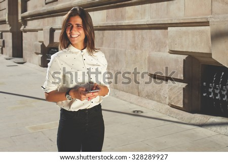 Portrait of smiling female walking on the street while holding mobile phone in the hands, young attractive woman having chatting conversation on smart phone, happy women using cellular with copy space - stock photo
