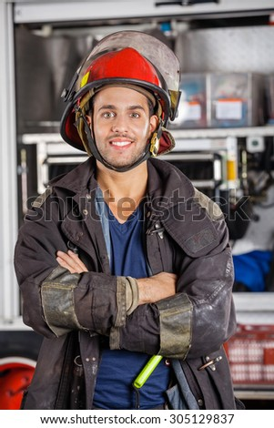 Portrait of smiling firefighter standing arms crossed against firetruck at station - stock photo