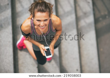 Portrait of smiling fitness young woman with cell phone outdoors in the city - stock photo
