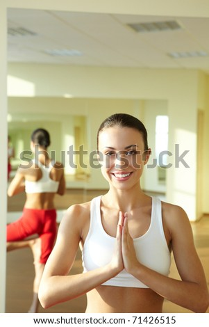 Portrait of smiling girl doing physical exercises and looking at camera - stock photo