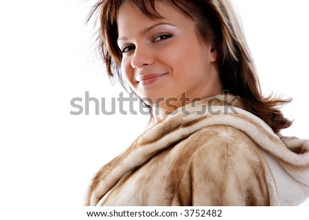 Portrait of smiling girl in fur coat on white background - stock photo