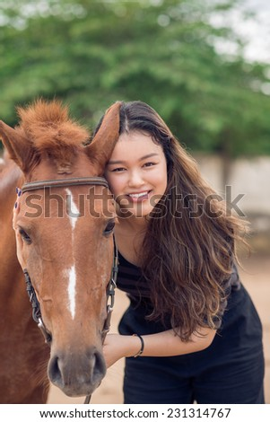 Portrait of smiling girl with a chestnut pony looking at the camera - stock photo