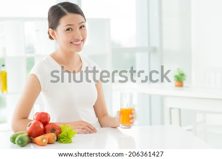 Portrait of smiling girl with a glass of orange juice - stock photo