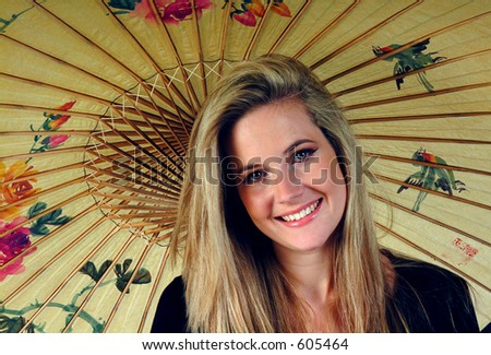 Portrait of smiling girl with Japanese paper umbrella. - stock photo