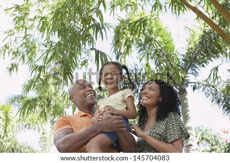 Portrait of smiling girl with parents enjoying in park - stock photo