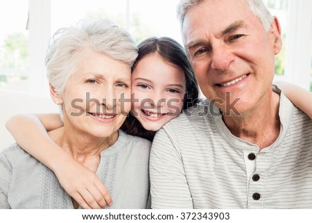 Portrait of smiling grandparents and granddaughter on the sofa - stock photo