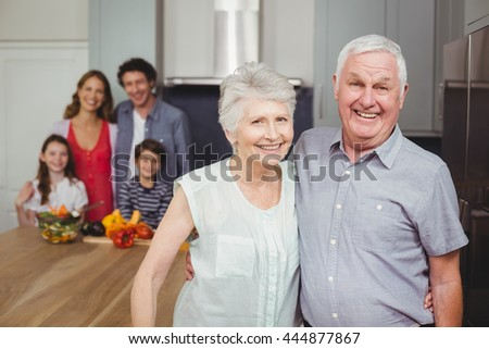 Portrait of smiling grandparents standing with family in kitchen at home - stock photo