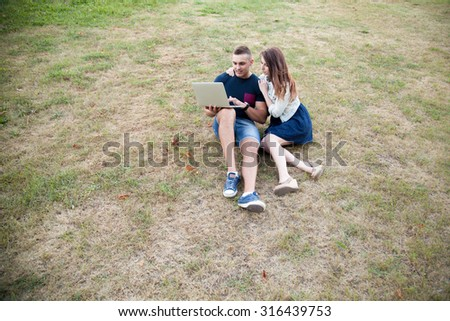 Portrait of smiling handsome young man and beautiful woman in casual clothes sitting on grass in park on summer day, working on laptop, looking at screen, full length, top view - stock photo