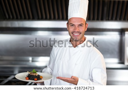 Portrait of smiling happy chef holding plate in commercial kitchen - stock photo