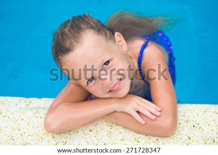 Portrait of smiling happy cute girl in outdoor swimming pool - stock photo
