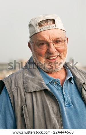 Portrait of smiling happy senior man outdoors looking at the camera - stock photo