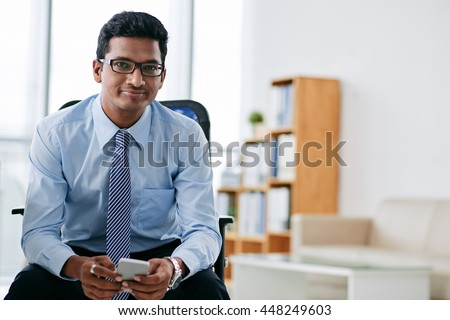Portrait of smiling Indian business person with smartphone sitting in office - stock photo