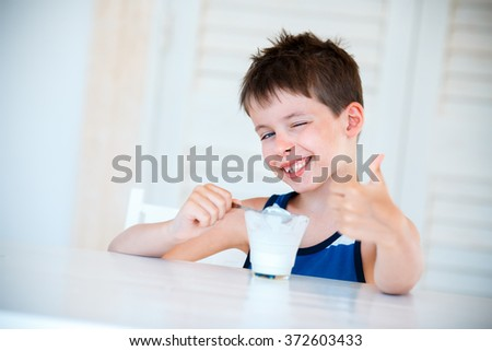Portrait of smiling little boy eating delicious yogurt - stock photo