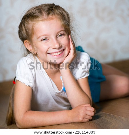 Portrait of smiling little girl laying on floor - stock photo