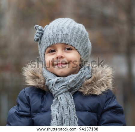 Portrait of smiling little girl with knit hat and scarf. - stock photo
