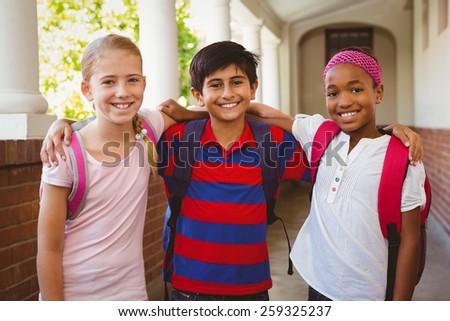 Portrait of smiling little school kids in school corridor - stock photo