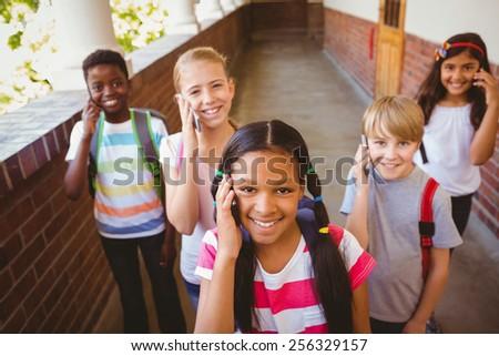 Portrait of smiling little school kids using cellphones in school corridor - stock photo