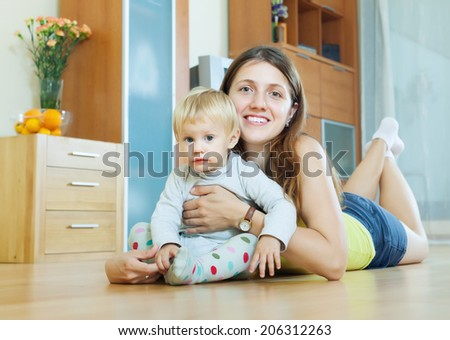 Portrait of smiling long-haired woman with toddler on on wooden floor in home interior - stock photo