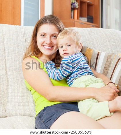 Portrait of smiling long-haired woman with toddler on sofa in home interior - stock photo