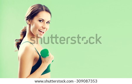 Portrait of smiling lovely woman in fitness wear exercising with dumbbell, over green background, with blank copyspace area for text or slogan - stock photo