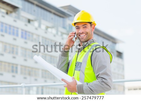 Portrait of smiling male architect with blueprints talking on mobile phone outdoors - stock photo