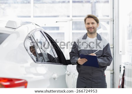 Portrait of smiling male automobile mechanic holding clipboard while standing by car in repair shop - stock photo