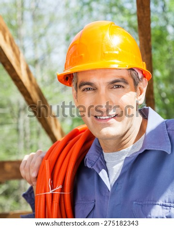 Portrait of smiling male construction worker carrying rolled pipe at site - stock photo