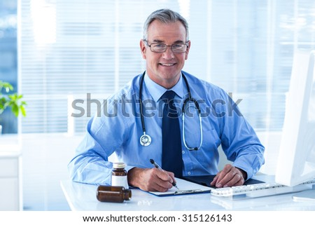 Portrait of smiling male doctor busy with paperwork at desk in hospital - stock photo