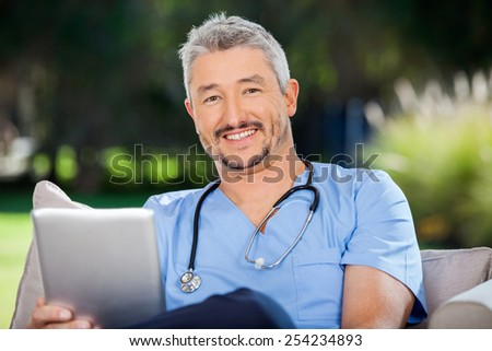 Portrait of smiling male doctor with tablet computer sitting at nursing home porch - stock photo