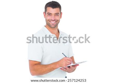 Portrait of smiling male handyman writing on clipboard over white background - stock photo