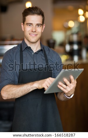 Portrait of smiling male owner holding digital tablet while standing in cafeteria - stock photo