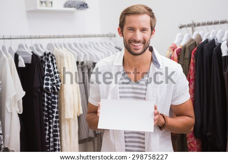 Portrait of smiling man holding blank sign and looking at camera at a boutique - stock photo