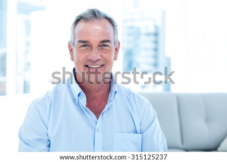 Portrait of smiling man sitting on sofa at home - stock photo