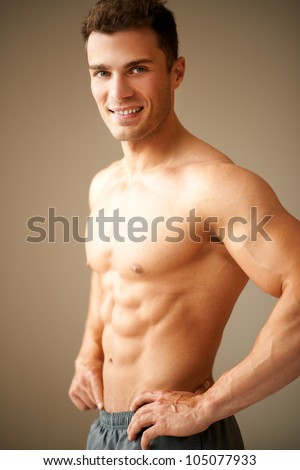 Portrait of smiling man with hand on his hips on brown background - stock photo
