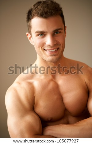 Portrait of smiling man with muscular arms crossed - stock photo