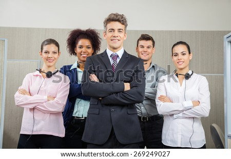 Portrait of smiling manager and team standing arms crossed at call center - stock photo