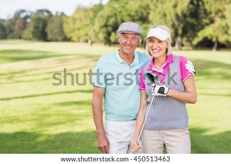 Portrait of smiling mature couple standing at golf course - stock photo