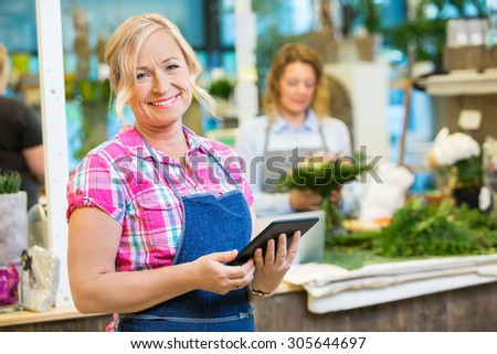 Portrait of smiling mature female florist holding digital tablet with colleague working in background at shop - stock photo