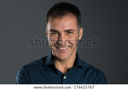 Portrait Of Smiling Mature Man On Grey Background - stock photo