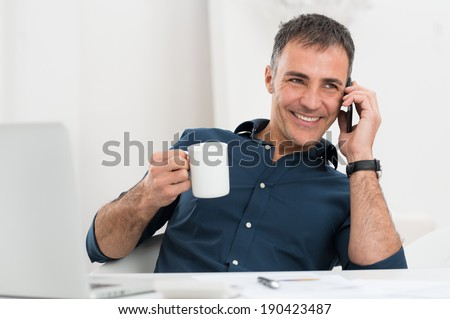 Portrait Of Smiling Mature Man Talking On Cellphone Holding Coffee Cup - stock photo