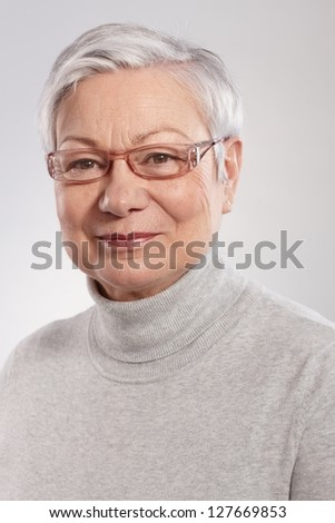 Portrait of smiling mature woman in polo-neck sweater and glasses. - stock photo