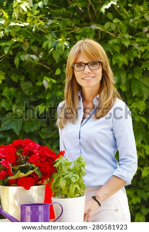 Portrait of smiling mature woman standing and working at flower shop. Small business owner.  - stock photo