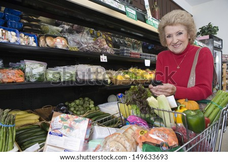 Portrait of smiling mature woman with cellphone while doing grocery shopping in supermarket - stock photo