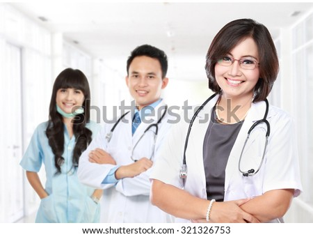 portrait of Smiling medical doctor with stethoscope with her staff. - stock photo