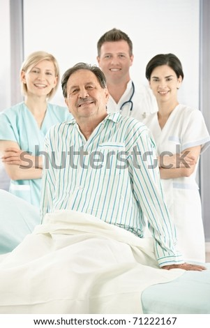 Portrait of smiling medical team with senior patient in hospital.? - stock photo