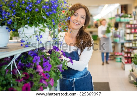 Portrait of smiling mid adult florist pushing flower shelves in shop - stock photo