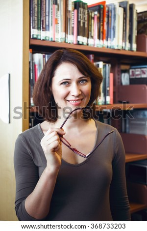 Portrait of smiling middle age mature Caucasian woman student with glasses in library, looking directly in camera, teacher librarian profession, back to school concept - stock photo