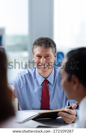 Portrait of smiling middle-aged businessman looking at the camera - stock photo
