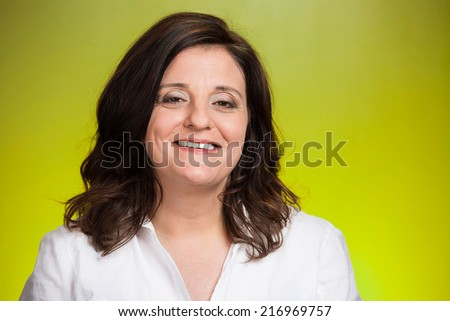 Portrait of smiling middle aged woman isolated on green background. Positive human emotions, facial expressions, feelings, life perception, attitude  - stock photo